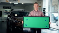 Man in Car Dealership Holding Green Sign video