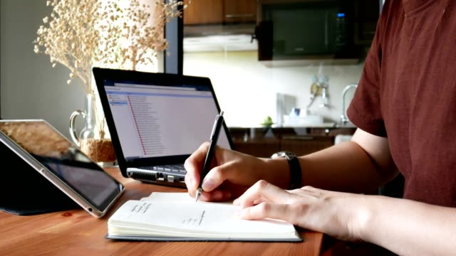 man in casual clothes writing on notebook at living room table - home office or working at home concept video