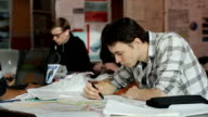 Man in chekered shirt develops plan of building in class video