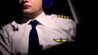 Man in civil aviation pilot uniform and headset navigating aircraft at cockpit video