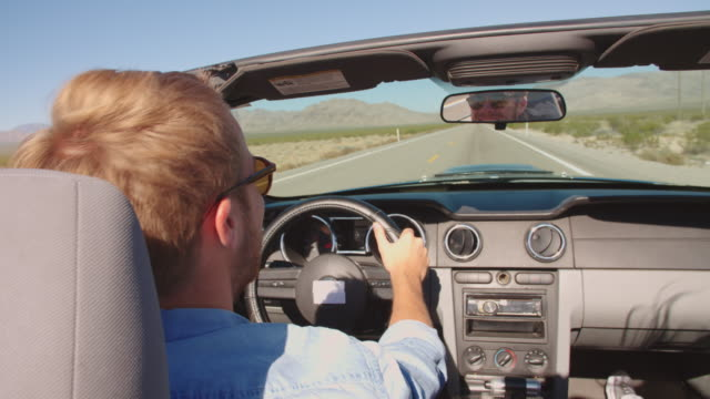 Man In Convertible Car Driving Along Open Road Shot On R3D video