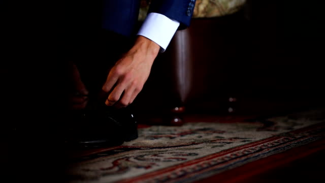 Man in dark blue jacket ties laces on black patent leather shoes video
