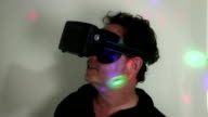 VR: Man in dim room reacts to VR experience with retro lighting effect video