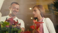 man in flower shop helping customer choosing plant video
