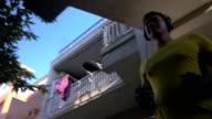 Man in headphones and sportswear leaving hotel video