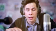 Man in headphones boring and lazy talking into microphone. video