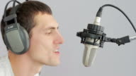 Man in headphones singing at studio microphone video