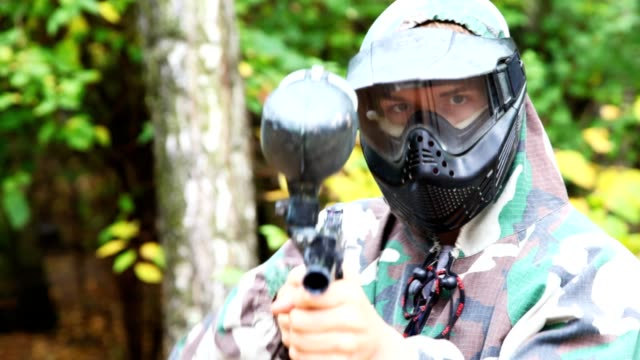 Man in helmet and mask with paintball gun aims video