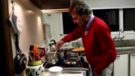 Man in his 60s cooking at home for the family. Grandfather cooking meal. Casual candid shot of older retired man cooking dinner. Man wearing red sweater cooking supper video