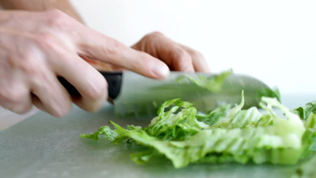 Man in Kitchen Chops Lettuce Wide video