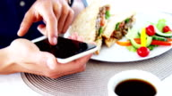 Man in lunch bar with smartphone and coffee video
