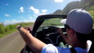 CLOSEUP: Man in luxury red convertible driving along the beach in sunny Hawaii video