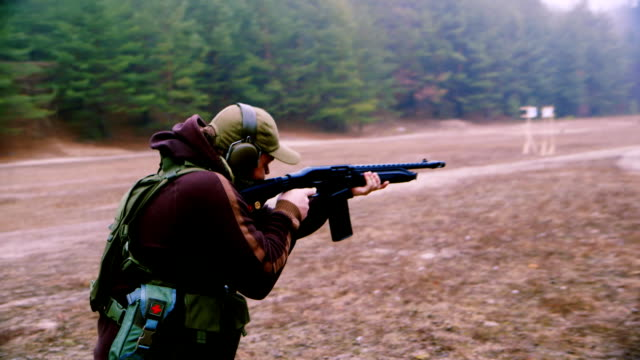 A man in military uniform with a gun shooting, hanheld back view video