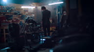 Man in motorcycle workshop building a bike video