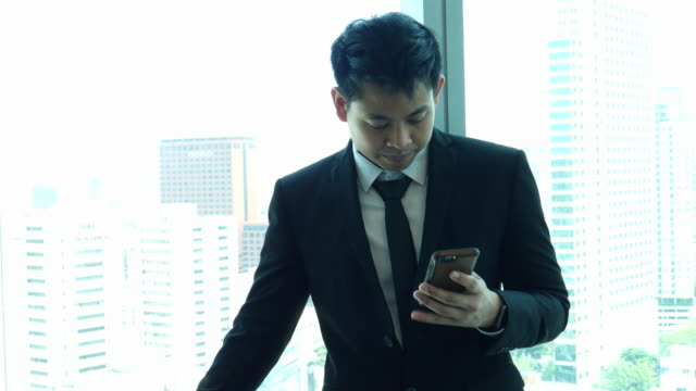 Man in penthouse using his smartphone video