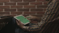 Man in plaid shirt uses touch screen tablet. video