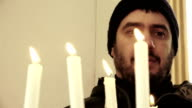 man in prayer insiede a church with candle light in foreground video