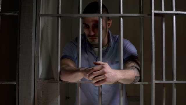 4K DOLLY: Man in Prison Jail Cell leaning on the bars video