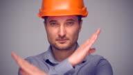 Man in protective helmet gesturing stop sign video