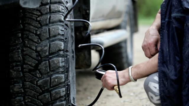 Man in raincoat pumping wheels of SUV at roadside video