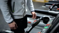 A man in shorts and a sweatshirt is engaged on a treadmill, increasing pace video