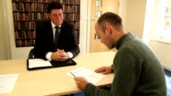 Man in solicitors signing Divorce papers video