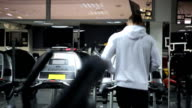 Man in sportswear is engaged on a treadmill in gym video