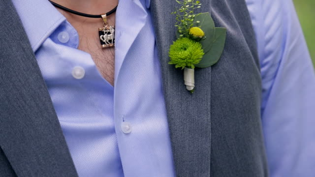 Man in suit corrects little groom bouquet on veil on wedding day video