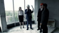 Man in suit, hard hat show woman, african american unfinished construction. Young couple, wife video