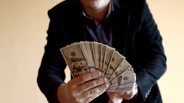 Man In Suit Holds Fan Of One Hundred Dollar Bills video