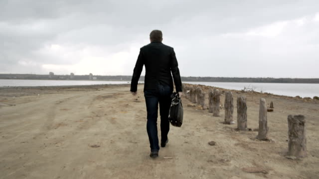 Man In Suit With Bag Walking In The Countryside In Slow Motion video