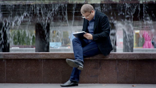 Man In Suit Working With Tablet Near Fountain On City Streets video