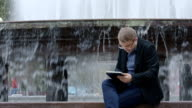 Man In Suit Working With Tablet Near Fountain video