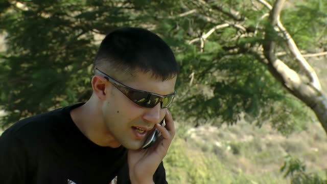Man in sunglasses talking on the phone video