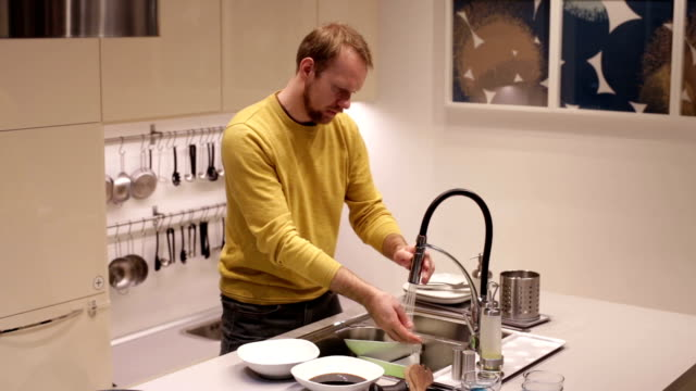 Man in the kitchen washing dishes in the sink video