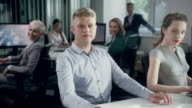 Man in the office, sitting behind his desk. Corporate Business video