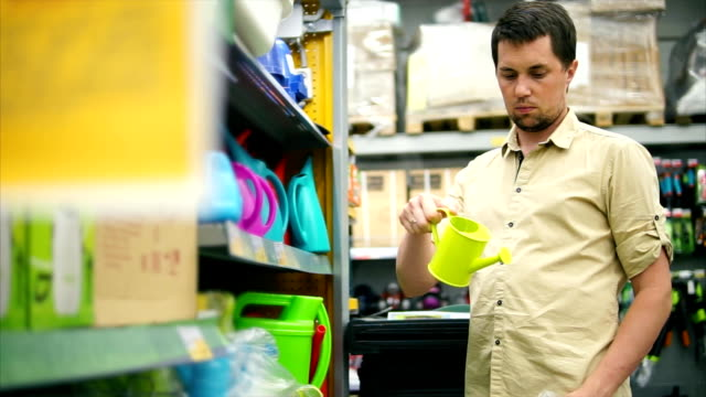 Man in the store. Customer taking mini watering can and wondering video