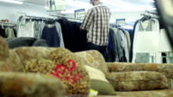 Man in thrift store shops for some new shirts video
