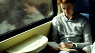 Man in train reading book video