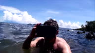 Man in tropical tidepool with VR headset gives thumbs up! video