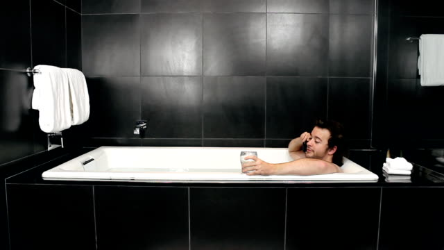 Man in tub with drink and phone - HD video