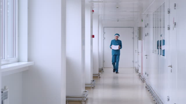 Man in uniform carry white paper in corridor. Male worker with pile of paper video
