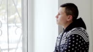man in warm sweater coughs standing at the window video