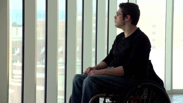 Man in wheelchair looking out a highrise window video