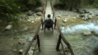 Man In Wheelchair On Footbridge In The Mountains video
