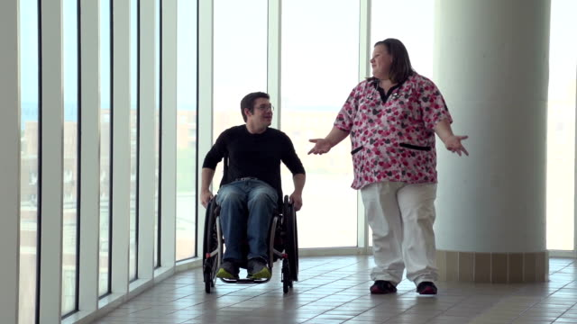 Man in wheelchair talking with nurse at hospital video