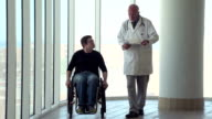 Man in wheelchair walking with doctor video