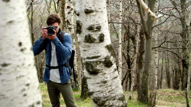 man in woods looking and shoot photos in camera.Following side.Real people Millennial traveller backpacker adult male photographer walking on rural field to shoot photographs in autumn season.4k video video