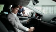 Man inspecting interior of the car in dealership video