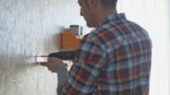 Man installing a tool rack to a wall using cordless drill. video